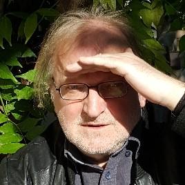 Mann um die 60 Jahre, schütteres blondes Har, 3-Tage-Bart, Brille, linke Hand an der Stirne, um die Augen vor der Sonne zu schützen,vor grünen Blättern