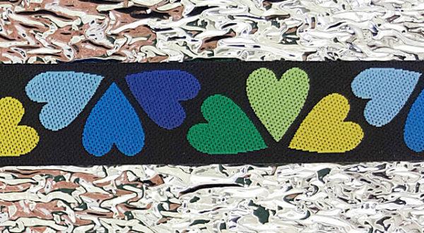 Schwarzes Webband mit blauen, grünen und gelben Herzen. Auf Alu.