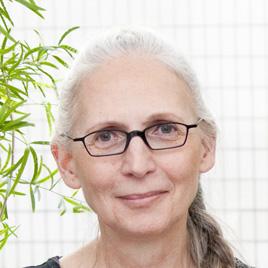 Portrait von Marie Wolf, einer Frau um die 60 Jahre, schwarze Brille, weißgraues langes Haar, zum Zopf gebunden, der, über die Schulter gelegt, rechts im Bild zu sehen ist.