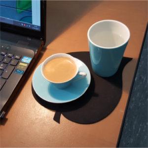 Moccatasse und Trinkbecher, beides graublau, auf Neoprenunterlage in Blattform, im Hintergrund Teilansicht Laptop.