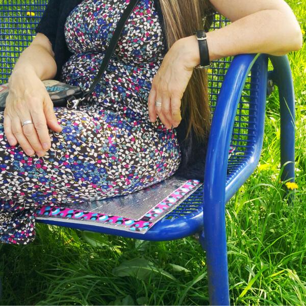 Bildausschnitt: Weibliche Person in geblümten Kleid, sitzt, unter Verwendung einer dazupassenden Sitzmatte, auf einer blauen Metallbank, welche in einer Wiese steht.