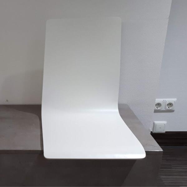Sehr stylische, minimalistische gestaltete sitzgelegenheit. Sitzfläche und Rückenlehne in einem Stück, weiß, auf dunkelgrauem Sockel montiert.