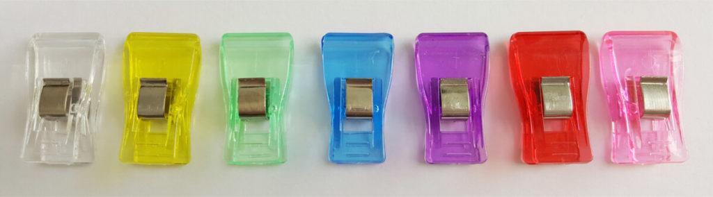 Kunststoff-Clips, nebeneinander vor weißem Hintergrund aufgereiht. Von links nach rechts in der Farben weiß, gelb, grün, blau, violett, rot und rosa.