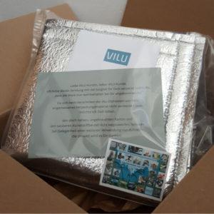 Sitzmatte von Vilu, zusammengefaltet und mit Infosblatt und Visitenkarte von VILU in Klarsichthülle in noch geöffnetem Versandkarton.