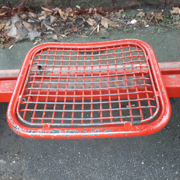 Rote, eiserne Sitzfläche mit dicker Metallumrandung und innliegender Gitterstruktur, auf ebenfalls roten Querstreben montiert.