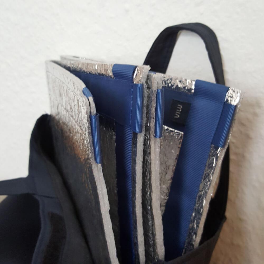 Teilansicht einer dunkelblauen Kunststofftasche, aus der eine blau VILU-Sitzmatte herausragt.