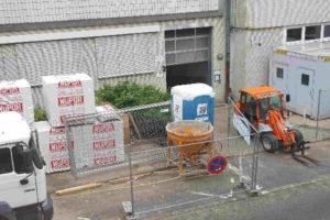 Baustellenansicht von schräg oben auf Absperrungen, Mischmaschine, Gabelstapler, Baustellen-WC und Baumaterialien.