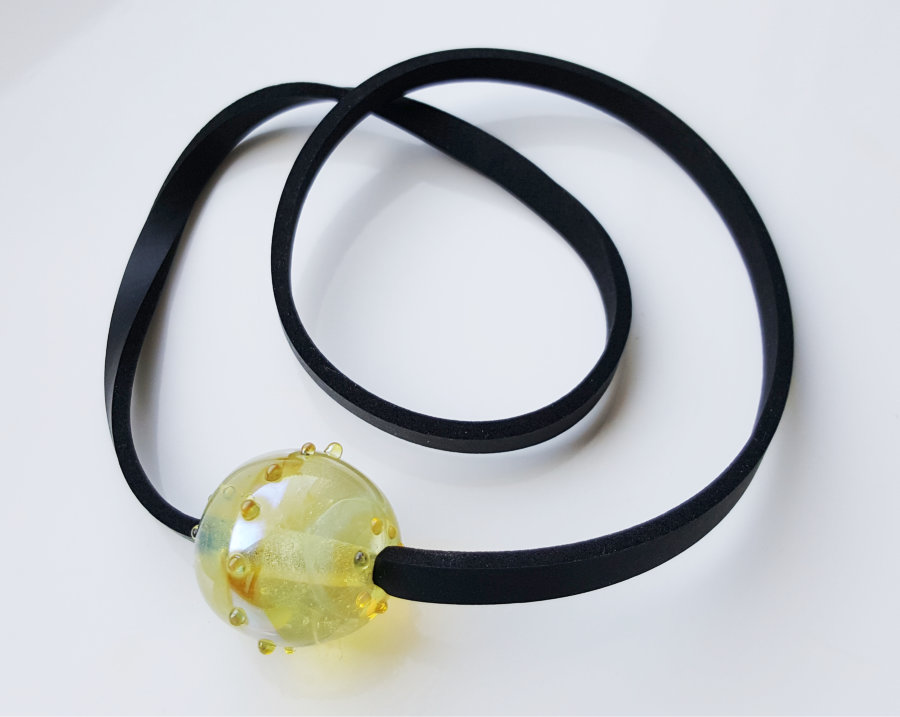 Schwarzes Halsband aus Neopren mit transparenter Glasperle in Gelbton aus dem Atelier Maren Kiss.