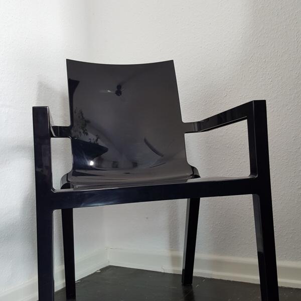 Kunststoffsessel in glänzendem Schwarz vor weißer Wand und Weißer Bodenleiste, auf schwarzem Boden.