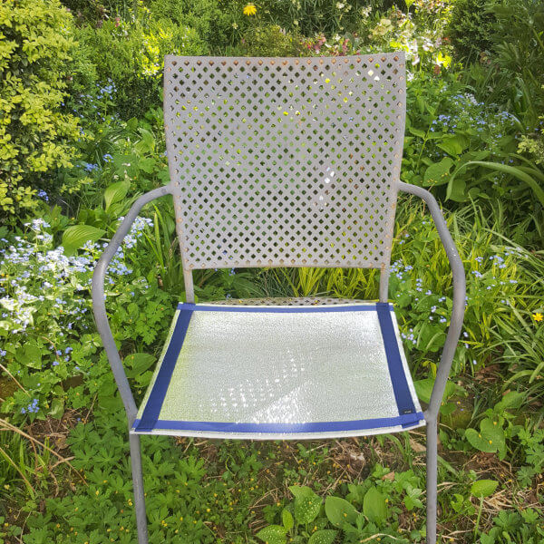 Eine Sitzmatte liegt auf der Sitzfläche eines metallenen Gartensessels, der an einer mit Frühlingsblumen bepflanzten Stelle steht.