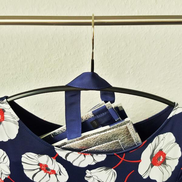 Eine zusammengefaltete, mit blauem Ripsband umnähte Sitzmatte von VILU auf einem Kleiderbügel, herauslugend aus dem Ausschnitt eines blauen, weiß-rot geblümten Kleides.