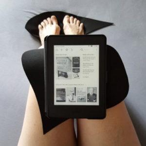 Sicht von oben auf abgewinkelte, nackte Beine. Die Zehen ruhen auf einer fischartig geformten Neoprenunterlage. Auf den Knien befindet sich eine weitere, von der Form her nicht identifizierbare Antirutschmatte, auf dem ein eBook liegt.