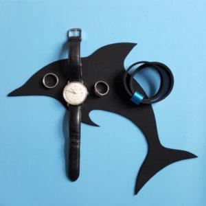 Auf hellblauem Hintergrund: Analog-Uhr, Schmuck aus Neopren mit blauem Metallring und 2 Silberringe auf schwarzer Neoprenfigur in Delphinform.