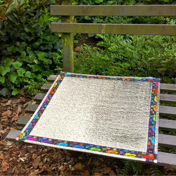 Mit buntem Ripsband umrandete Alu-Sitzmatte auf einer dunkel gestrichenen Holzbank, die am Wegesrand vor einer grünen Bepflanzung steht. Bildausschnitt.