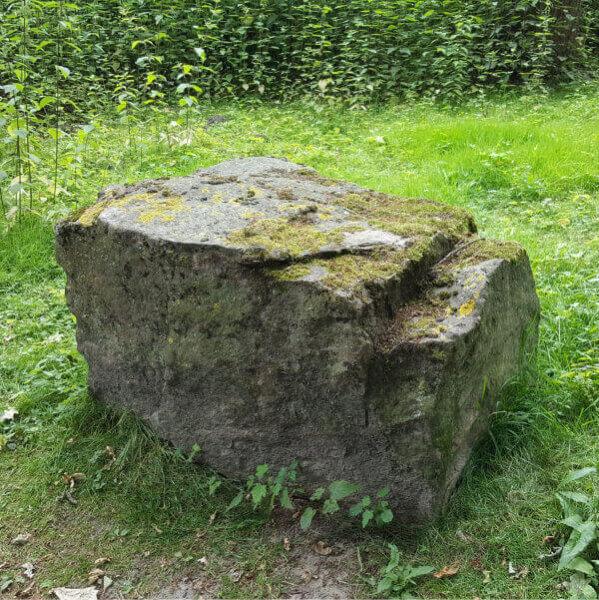 Großer Naturstein auf Wiese mit zum Sitzen geeigneter Oberfläche.