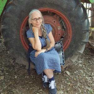 Nahaufnahme eines Traktorreifens, auf dessen Felgen-Innenrand eine weißhaarige Frau mit langem Zopf in blauweißgestreifter Kleidung auf einer Alu-Sitzmatte sitzt.