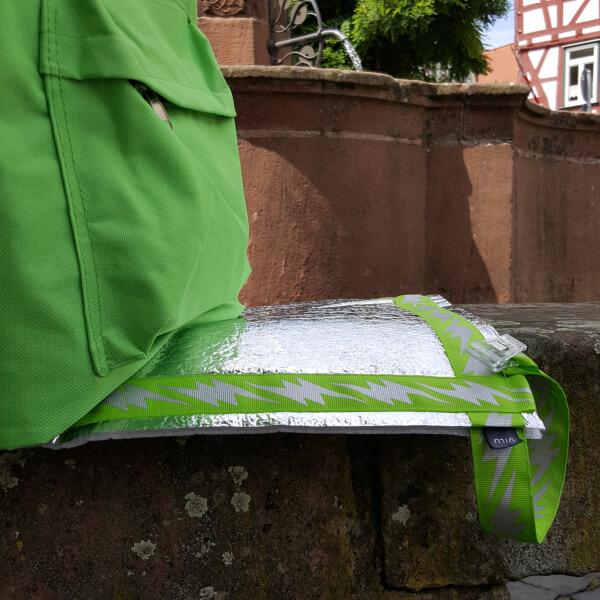 Bildausschnitt. Im steinernen Sitzbereich rund um einen Brunnen Im Vordergrund links ein hellgrüner Rucksack, rechts davon im Zentrum des Bildes eine mit hellgrün/silbernem Ripsband umrandete Alu-Sitzmatte.