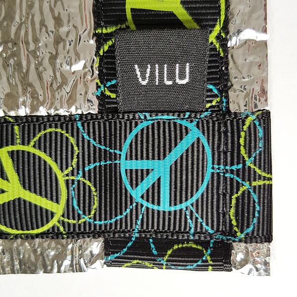Ecke einer Alu-Sitzmatte von VILU. Ripsband Peacezeichen in grün und blau, VILU Logo-Wäschelabel weiß auf schwarz.