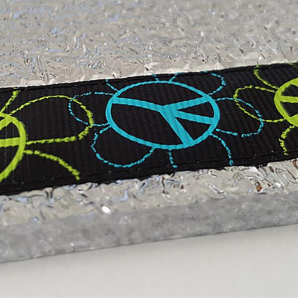 Sitzkissen von VILU mit Peace-Ripsband. - Seitenansicht: Seitenansicht: Zu sehen ist, dass die VILU-Sitzunterlage aus 2 PE-Schaum-Matten besteht.