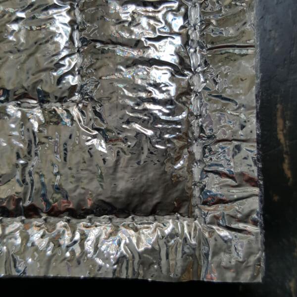 Bildausschnitt. Ecke einer Alu-Sitzmatte von VILU. Zu sehen ist die Rückseite.