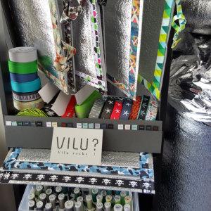 """Hängend und liegend fertige VILU-Sitzmatten, Alumaterial auf Rolle, Näheseiden, Polyesterbänder auf Rollen und Bandkarten, alle 22 VILU-Wäsche-Logolabels auf einer Musterkarte; mittig: Hangtag mit dem Aufdruck """"VILU? vilu rocks!"""""""