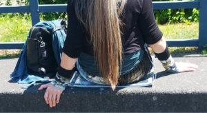 Person mit langem, dunkelblondem Haar, vom Rücken abwärts von hinten zu sehen, auf Sitzmatte auf Steinbank, linksseitig abgestellter Rucksack, Kleidung und Alu-Matte mit grün-blau-Tönen.