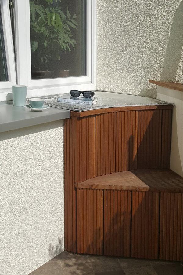 Zu sehen ist ein stufenförmiger Aufbau aus Holz zu einer Fensterbank, auf der man dank VILU-Matte mit Alufolierung warm sitzen kann.