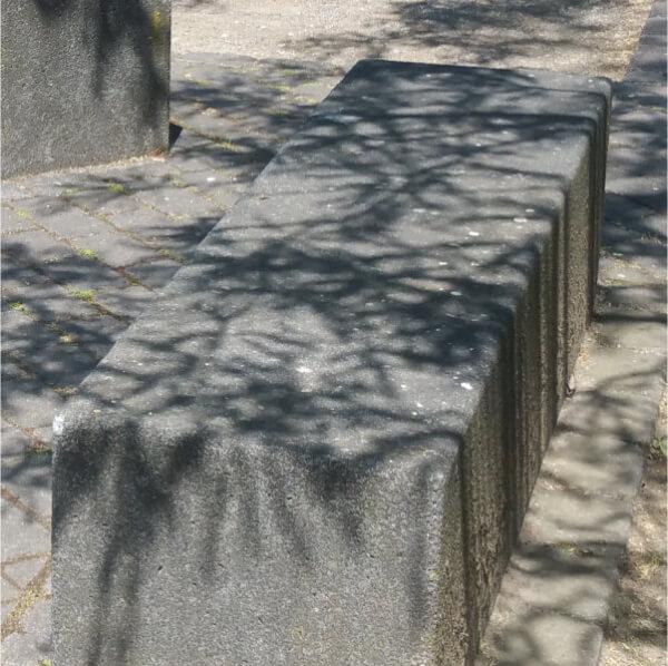Grauer Sitzstein, worauf die Schatten einer darüberliegenden Baumkrone das Sonnenlicht verdecken..