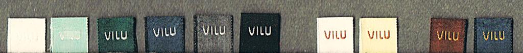 10 der 22 verschiedenen VILU-Wäsche-Logolabels, vor dunkelgrauem Hintergrund nebeneinander aufgereiht.