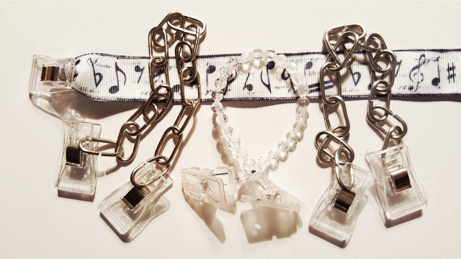 quer ein clipband aus Rips, Motiv musikalische Zeichen, darauf liegend 3 Arten von Doppelclipbändern aus Metall bzw. Kunststoff.