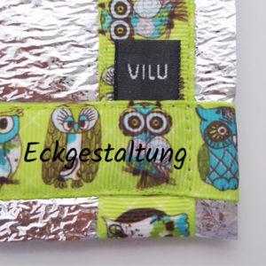 Ecke einer Alu-Sitzmatte von VILU. Ripsband Eulen auf grün, VILU Logo-Wäschelabel weiß auf schwarz.