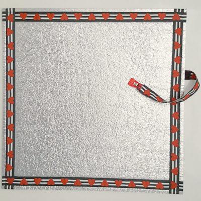 Vollansicht: Alu-Sitzmatte von VILU. Ripsband mit roten Herzen auf schwarzweißem Untergrund. Oben zu sehen das integrierte Clipband.