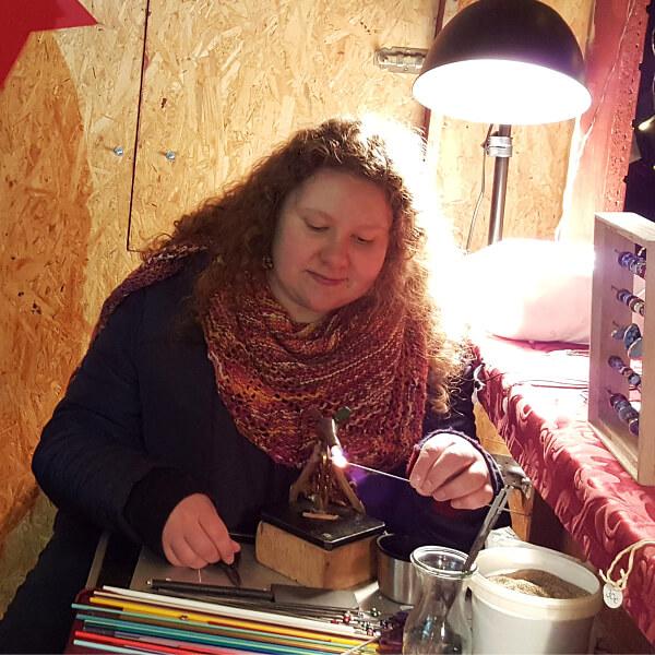 Maren Kiss beim Glasperlendrehen an ihrem winzigen Arbeitsplatz in einer Weihnachtshütte.