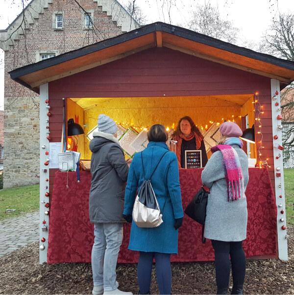 Drei Frauen vor der Weihnachtshütte im Gespräch mit Maren Kiss.