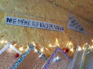 """Vilu-Slogan an der Rückwand der Weihnachtshütte: """"Nie mehr auf kaltem sitzen - mit der Thermo-Sitzmatte."""