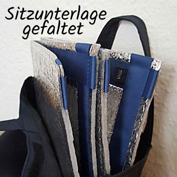 Gefaltete Sitzmatte mit blauer Ripsband-Umrandung, aus einer Stofftasche lugend.