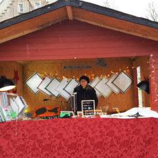 Weihnachtshütte, rot-silber geschmückt und u. a. mit Alu-Sitzmatten und Schmuck als Produktauswahl, samt Verkäuferin in der Mitte des Bildes.