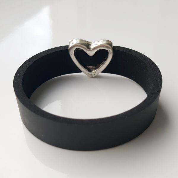 Armband aus Neopren mit Schiebeperle aus Zamak versilbert in Herzform. Ansicht auf die Hinterseite des Schmuckelements.