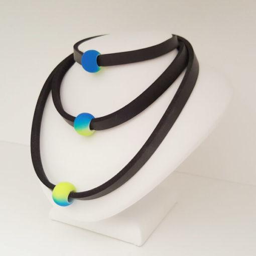 Schwimmschmuck mit Acrylperle blaugelb von VILU für Arm, Hals und/oder Fuß auf einer kleinen Schmuckbürste.