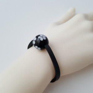 Handgedrehte Perle mit Motiv weiße Blüten auf schwarz, an einem Neoprenband um das Handgelenk einer Modelhand.