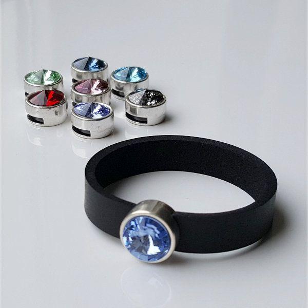 Im Vordergrund: Armband aus Neopren mit einem hellblauen, leicht ins Lilafarbene gehenden Glaselement in Schiebeperle. Links im Hintergrund 7 verschiedenenfarbige Schmuckperlen der gleichen Art, lose zusammengestellt.