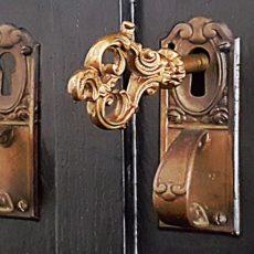 Ausschnitt aus einer alten Kommodenfront mit 2 nebeneinander liegenden Türschloss Beschlägen aus Messing - links nur zur Zierde, also ohne Schlüsselloch, rechts mit einsteckenem, verziert gestaltetem Schlüssel.