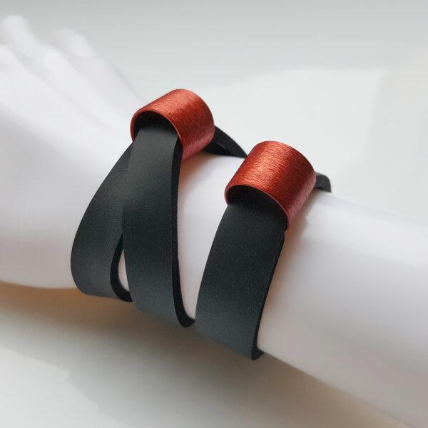 Zwei breite schwarze Neoprenbänder auf einer Dekohand mit jeweils einem roten, zylinderförmigen Schmuckelement.