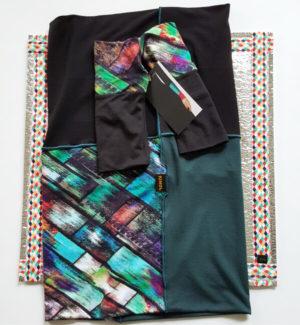 Bunte Armstulpen und bunter Mini, beides in türkisfarbenem Grundton, kombiniert mit schwarz auf Sitzkissen von VILU in buntem Rautendesign