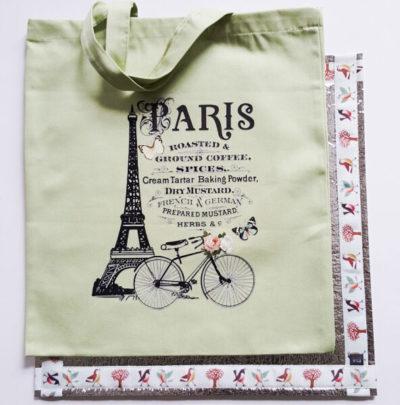 """Auf einem Sitzkissen mit dem Motiv """"Vogelwelt"""" liegt eine Stofftasche mit einem Paris-Motiv."""