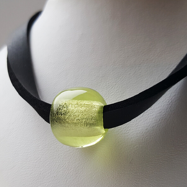 Teilansicht: zitronengelbe Glasperle auf gedrehtem Neoprenhalsband auf Schmuckbüste