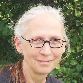 Marie Wolf: Weißes Haar, offenbar lang und hinten zu einem Pferdeschwanz zusammengebunden, denn etwas Haar lugt seitlich hervor, schwarze Brille, Anfang 60 Jahre