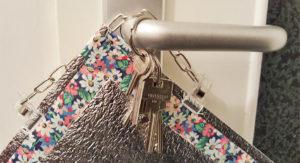 Teilansicht einer Alu-Sitzmatte mit Blumenmotiv, die mittels Doppelclipband über einem Türgriff hängt, an dem auch ein Schlüsselbund übergestreift ist.
