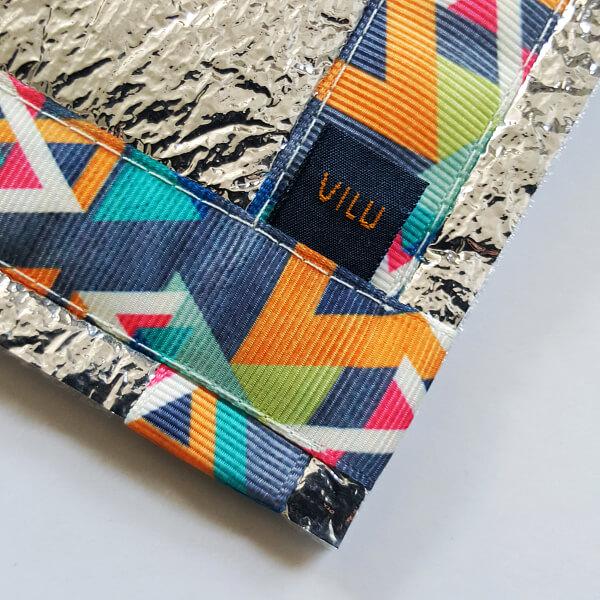 Sitzkissen-Ausschnitt Ecke mit VILU-Logo mit Ripsbanddesign buntes geometrisches Muster