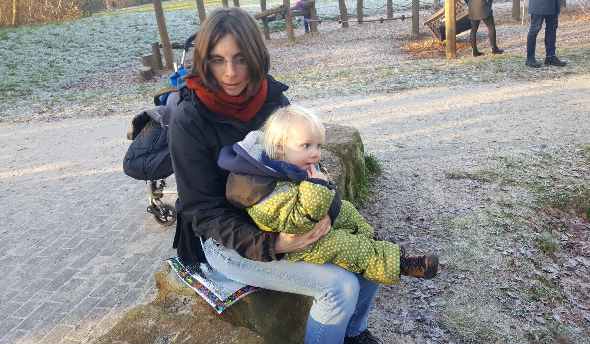Mutter mit Kleinkind auf Spielplatz, sitzend auf einem Stein unter Verwendung eines VILU-Sitzkissens